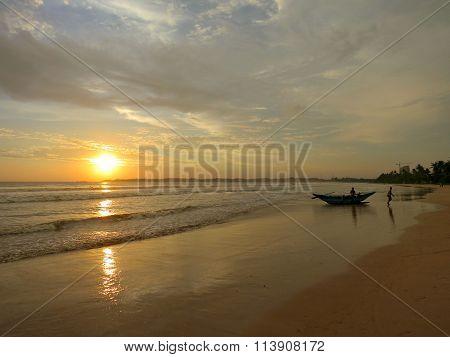 Sunset beach with fisherman boat silhouette in water, Sri Lanka