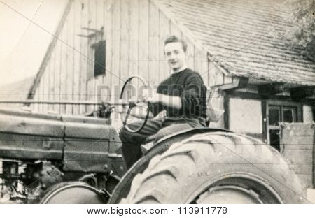 GIESMANNDORF, GERMANY, CIRCA THIRTIES - Vintage photo of young man on tractor