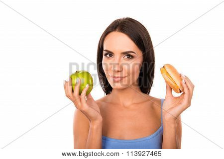 Happy Young Woman Deciding Between An Apple And Burger