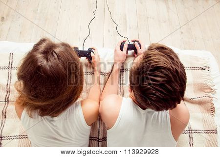 Upper View Of Couple In Love Playing Video Games With Joysticks On The Bed