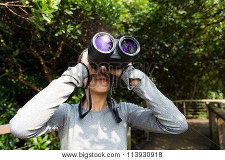 Woman looking though binoculars at jungle