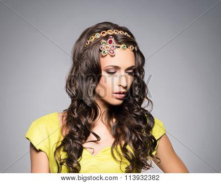 Gorgeous, sensual brunette wearing golden luxury coronet over grey background.