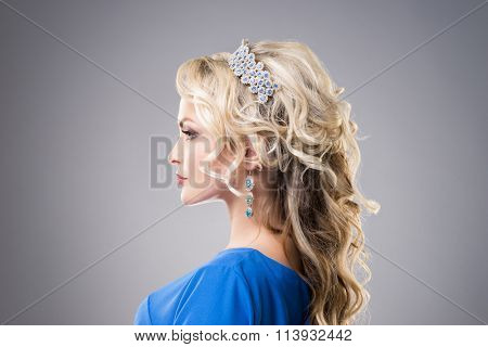Side view of beautiful, young lady wearing sapphire coronet and earrings over grey background.