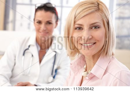 Close up of happy blonde casual caucasian female patient at doctor's medical office. Smiling and looking at camera.