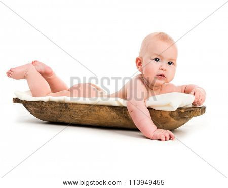 five-month old baby girl in a wooden trough isolated on a white background