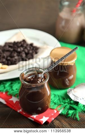 Chocolate dessert in small glass jars and morsels on plate, on wooden background