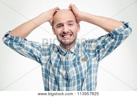 Desperate upset young man in plaid shirt with hands over head isolated on white background