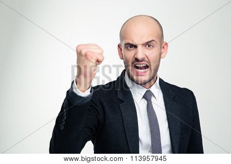 Irritated furious young business man in formalwear shouting and showing fist over white background