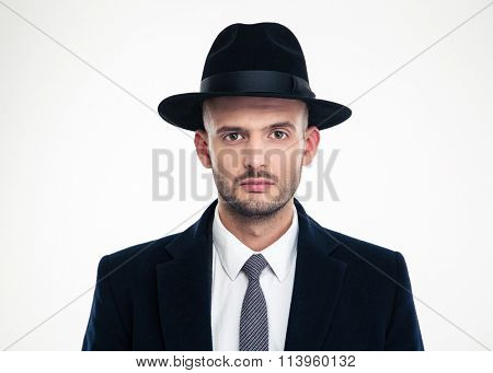 Portrait of handsome serious young businessman in black suit and hat looking at camera over white background