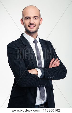 Cheerful attractive young business man standing with crossed arms over white background