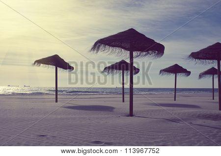 Wooden Sun Umbrellas Silhouettes On The Sea Beach. Vacation Concept In Vintage Color Tone. Costa Dor