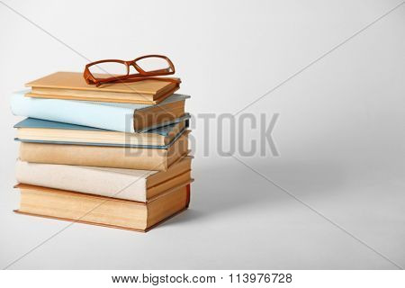 Pile of books and eyeglasses on it isolated on white background