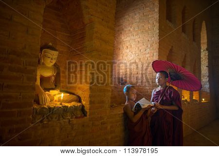 Unidentified Buddhism neophyte prays in Buddihist temple.