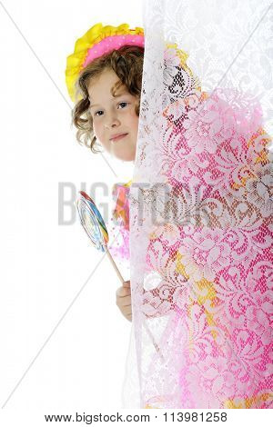An elementary actress peeking from behind a lace curtain with a giant lollipop as she's prepared to play Shirley Temple.  On a white background.