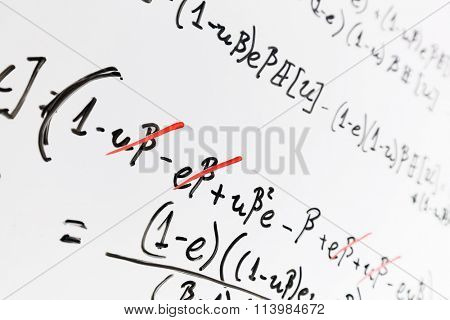 Complex math formulas on whiteboard. Mathematics and science with economics concept. Real equations, symbols handwritten by a professional.
