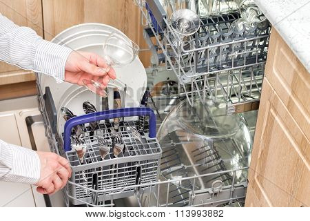 Man takes a clean glass from the dishwasher