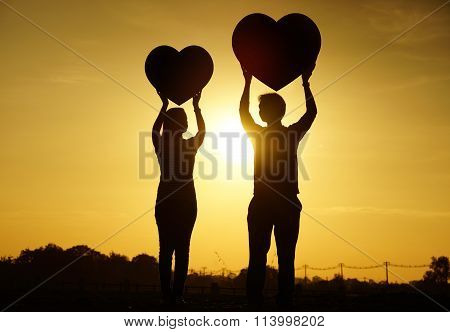a man and a woman holding big red hearts with sunset silhouette background