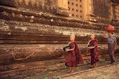 Southeast Asian young Buddhist novice monks walking morning alms in Old Bagan, Myanmar poster