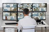 Rear view of security system operator looking at CCTV footage at desk in office poster