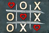 Vintage chalkboard with Tic Tac Toe Game Competition XO Win created of wood letters and red hearts letters O and X replaced with red heart shapes Challenge and Love Always Wins Concept poster