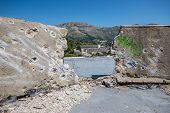 bullet holes on the roof of abandoned hotel in former Tourist Complex of Kupari village Croatia poster