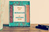Retro effect and toned image of a vintage photo frame next to fountain pen and notebook . Motivational quote written with typewriter font THERE ARE MIRACLES ALL AROUND YOU poster