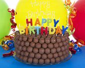 Whopper of a Chocolate Birthday Cake decorated with candy malt balls and Happy Birthday Candles. Balloon background. Fast and easy home made cake for children or adult birthday party poster
