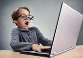Shocked and surprised boy on the internet with laptop computer concept for amazement, astonishment, making a mistake, stunned and speechless or seeing something he shouldnt see poster