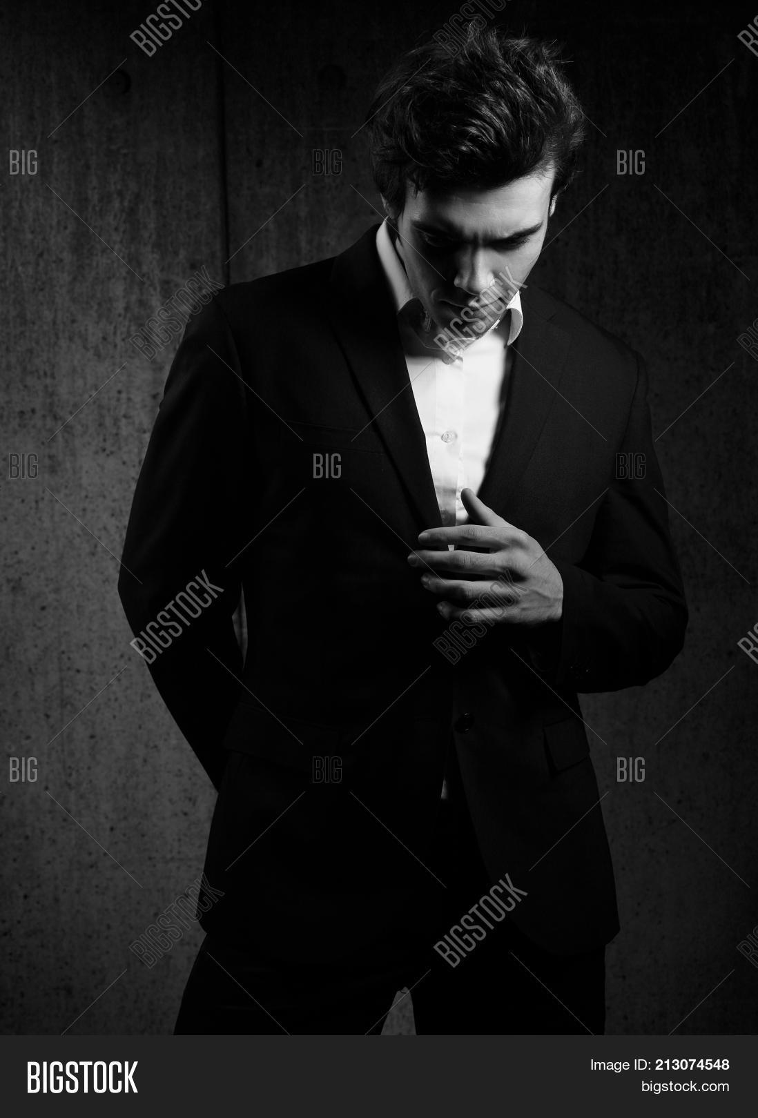 1f6d014b Handsome male model posing and looking down in fashion suit and white style  shirt on dark shadow background. Portrait. Black and white