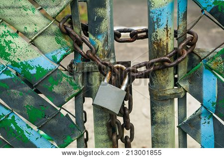 Empty lot protected from possible invasions by a chain and a padlock.