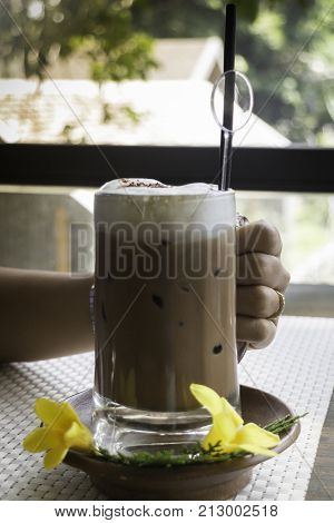 Hand on iced coffee at balcony wooden table stock photo