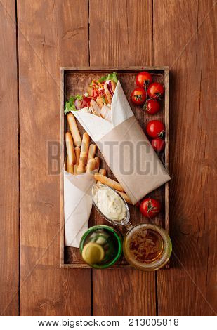 Shawarma on a tray. Fast food. Eastern food. Street food. Shaverma, shawarma, shaurma, pita gyros. Shawarma lying on pita bread and decorated with tomatoes, bread sticks, sauce and beer.