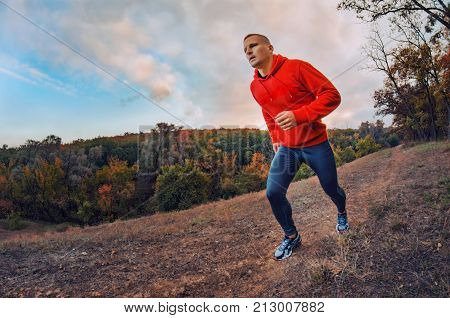 Thleticr Jogger  Runs On The Colorful Red Autumnal Forest Hill With Sunset Dramatic Sky