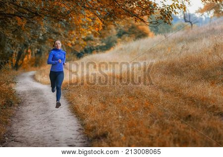 Young Slim Athleic Jogger Woman Runs Along The Path  On The  Beautiful  Autumnal Forest.