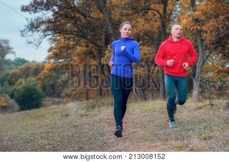 A pair of jogger in black leggins and color jacket fast run along the path on the colorful autumnal forest hill. Photo show active healthy lifestyle.