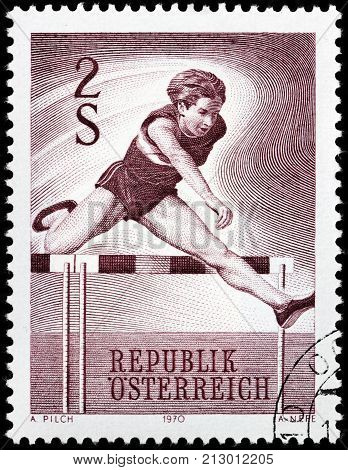 LUGA RUSSIA - AUGUST 20 2017: A stamp printed by AUSTRIA shows Hurdler. Hurdling is the act of running and jumping over an obstacle at speed circa 1970