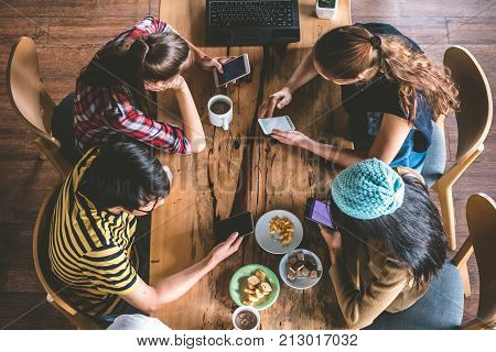 Group of Friends are chitchatting during meal. Teenage using mobile phone in cafe.