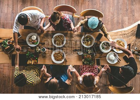 Group of friend pray before having nice food and drinks enjoying the party and communication Top view of Family gathering together at home for eating dinner.