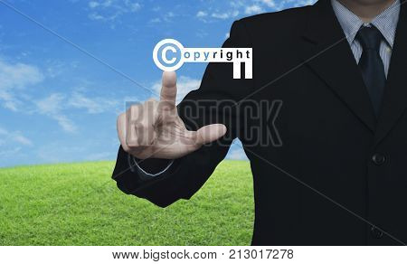 Businessman pressing copyright key icon over green grass field with blue sky Copyright and patents concept