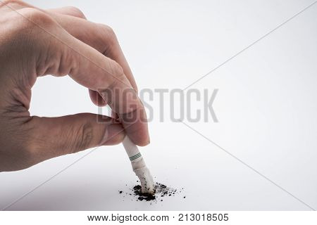 A hand push the cigarette stub on white background Symbolic stop smoking concept Free space for text