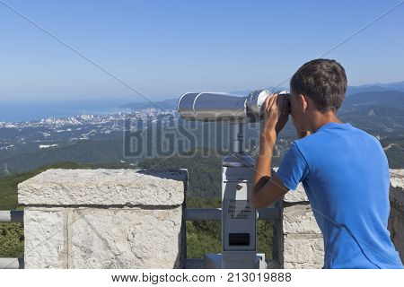 Sochi, Hosta District, Krasnodar region, Russia - July 14, 2016: Boy looks at the resort city of Sochi through binoculars from a tower on the mountain Big Ahun