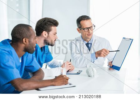 handsome general practitioner showing clipboard for colleagues
