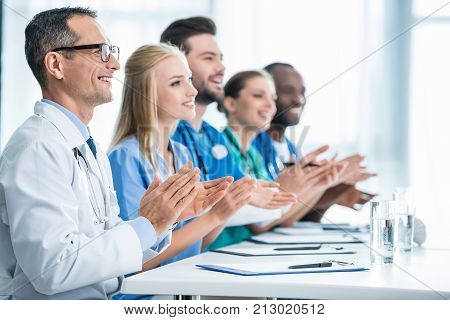 Doctors Sitting At Table And Clapping