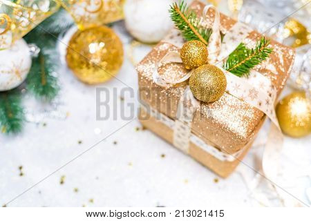 New Year's gift in a golden box, decorated with bart, Christmas tree branches and Christmas toys, Christmas Present with Gold Ribbon and Gold Christmas Decorations
