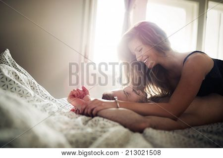Woman and man playing domination games in bed together