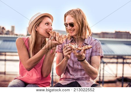 Young couple sitting outdoors and eating pizza.Fast food.