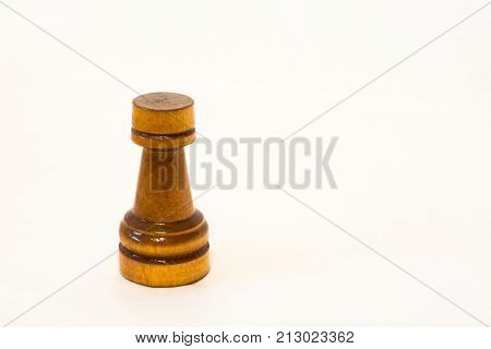 The black chess rook of wood on the white background