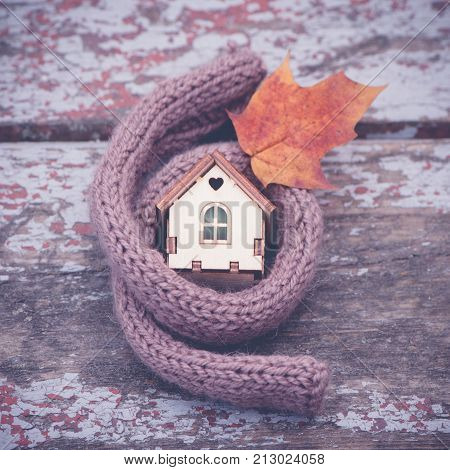 toy house is wrapped in a warm scarf with an autumn leaf. The concept is warm cozy loving protecting the house. We prepare the house for the cold. Square