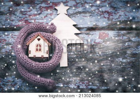 Toy house is wrapped in a warm scarf it's snowing. in the background a fur-tree. The concept is warm cozy loving protecting the house. We prepare the house for the cold.