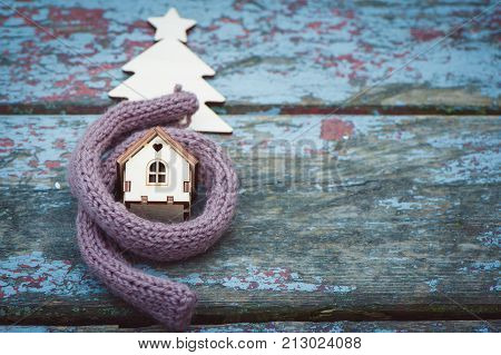 Toy house is wrapped in a warm scarf it's snowing. in the background a fur-tree. The concept is warm cozy loving protecting the house. We prepare the house for the cold. Space for text